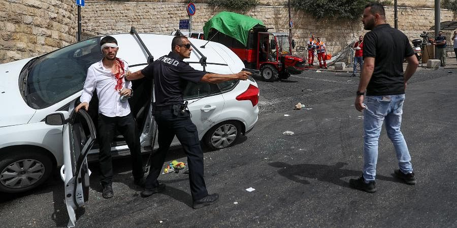 An Israeli police officer protects a Jewish driver who was attacked by Palestinian protesters near Jerusalem's Old City.