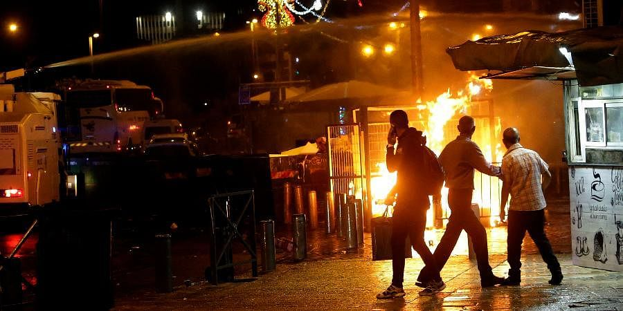 An Israeli police water cannon is deployed near the Damascus Gate to the Old City of Jerusalem as a fire burns during clashes between police and Palestinian protesters.