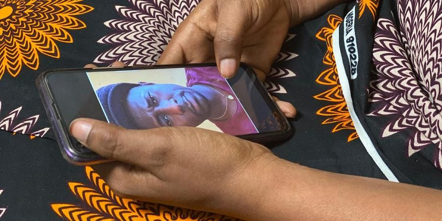 A woman holds her phone displaying a photo of former World Health Organization doctor Boubacar Diallo, of Canada, during an interview in the eastern Congo town of Goma