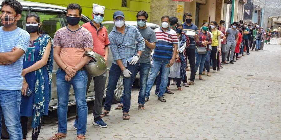Beneficiaries wait in a queue to recieve COVID-19 vaccine dose at a health centre.