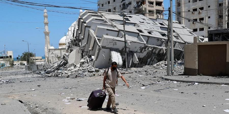 A man pulls his luggage while passing the rubble of a destroyed building which was hit by Israeli airstrikes, in Gaza City
