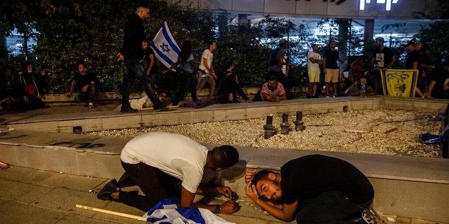 Jewish nationalist demonstrators take cover during a barrage of rockets fired from the Gaza Strip toward central Israel, in the Israeli town of Ramla.