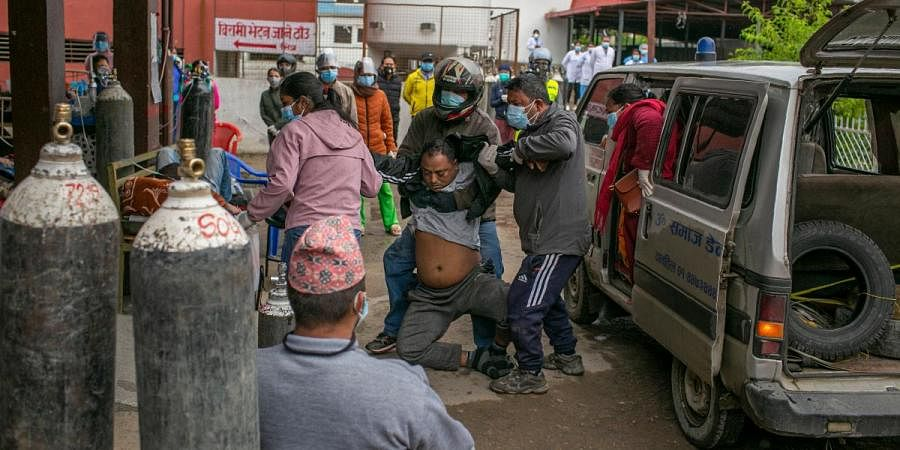 Family members struggle to carry a COVID-19 patient towards the emergency ward of a hospital just before he was declared dead by the doctors in Kathmandu