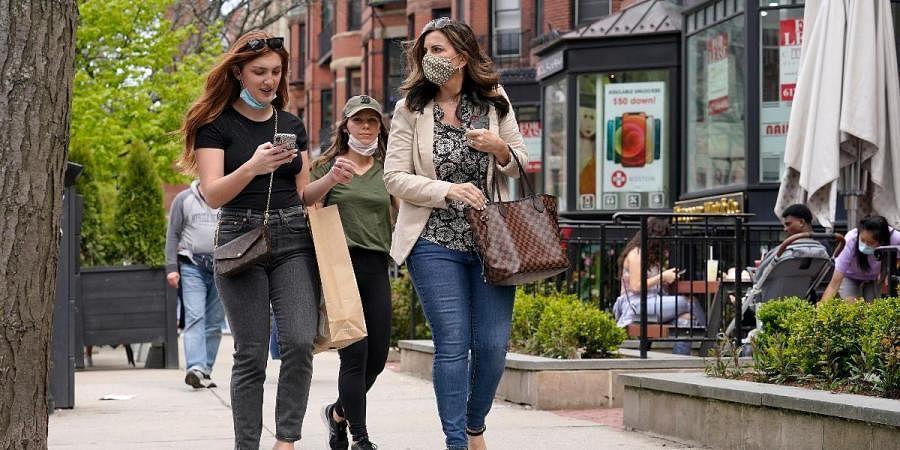 Pdestrians walk along Boston's fashionable Newbury Street without wearing masks