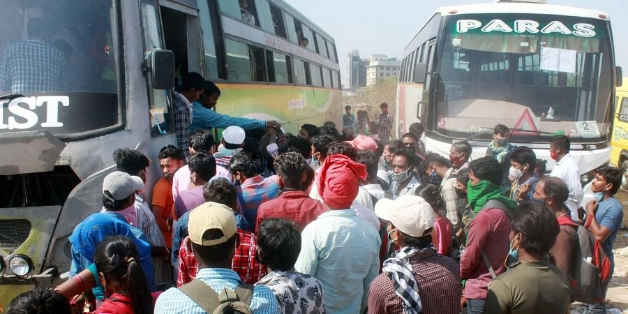 Migrant labourers try to board a bus to their native places in Uttar Pradesh and Bihar, from Gurugram, on Sunday. (Photo | PTI)
