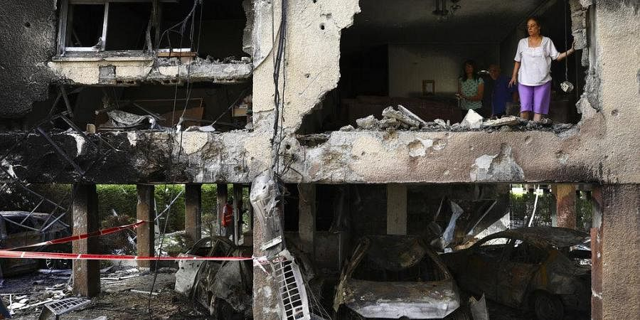 Members of Sror family inspect the damage of their apartment after it was hit by a rocket fired from the Gaza Strip over night in Petah Tikva, central Israel, Thursday, May 13, 2021. (Photo | AP)