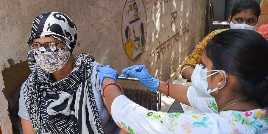A medic administers COVID-19 vaccine dose to a beneficiary at a vaccination center