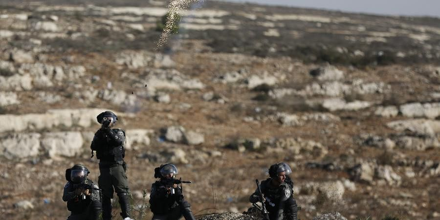 Israeli troops fire teargas as they clash with Palestinians during the protest against the U.S. announcement that it no longer believes Israeli settlements violate international law., at checkpoint Beit El near the West Bank city of Ramallah, Tuesday.