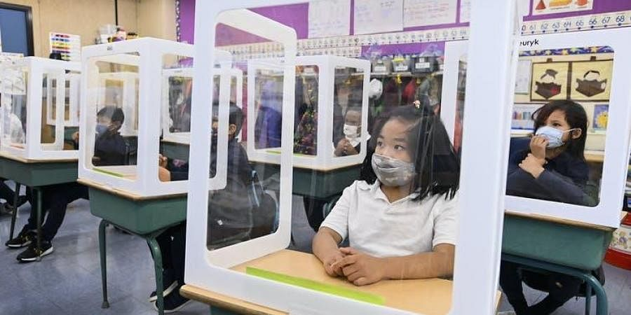 Children wearing masks sit behind screened-in cubicles in their classroom at a Toronto school during the COVID-19 pandemic