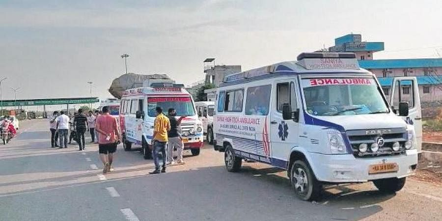 Ambulances line up outside the Pullur Toll Plaza after being denied entry into the State