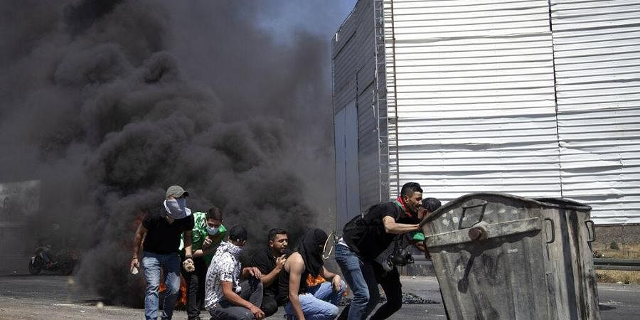 Palestinian demonstrators take cover during clashes with Israeli forces at the Hawara checkpoint, south of the West Bank city of Nablus