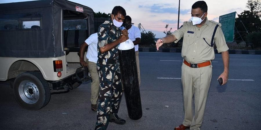 Kurnool SP Fakeerappa Kaginelli arranges an oxygen cylinder to a patient whose ambulance was stopped at Pullur toll plaza on Friday. (Photo | EPS)