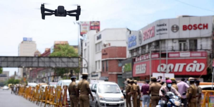Police personnel using drones to monitor vehicular and public movement in the city