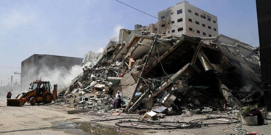 Workers clear the rubble of a building that was destroyed by an Israeli airstrikethat housed The Associated Press, broadcaster Al-Jazeera and other media outlets, in Gaza City