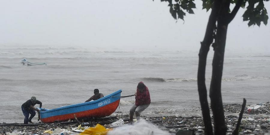 Fishermen pull their boat ashore to a safe place during formation of cyclone Tauktae in Mumbai