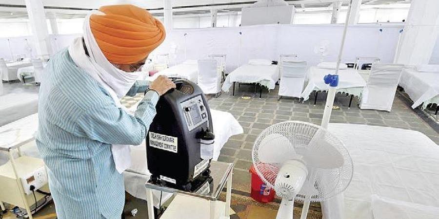 A volunteer checks an oxygen concentrator machine.