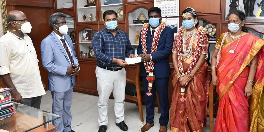 Sharinraj and Surya giving their donation to district collector | Express