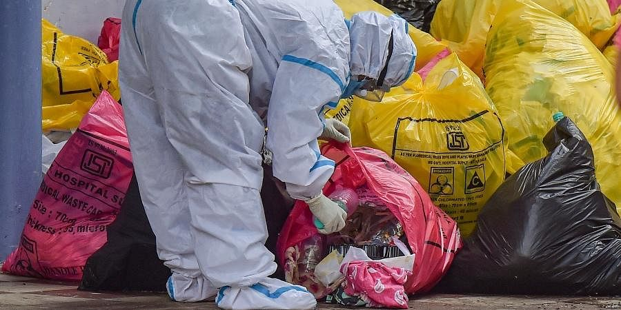 A medical worker sorts medical waste before sending for disposal, at a COVID-19 hospital