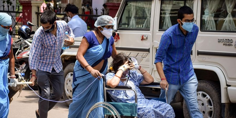 Relatives carry a COVID-19 positive patient on oxygen support to Swaroop Rani Nehru Hospital, amid a countrywide hike in coronavirus cases, in Prayagraj, Wednesday