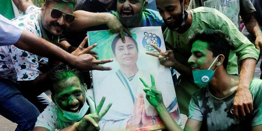 TMC supporters pose with a poster of Bengal CM Mamata Banerjee (Photo | PTI)