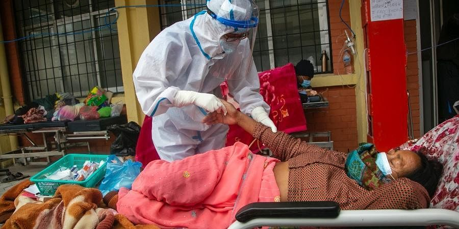 Nepalese paramedics treat a COVID-19 patient outside an emergency ward of a government run hospital in Kathmandu,