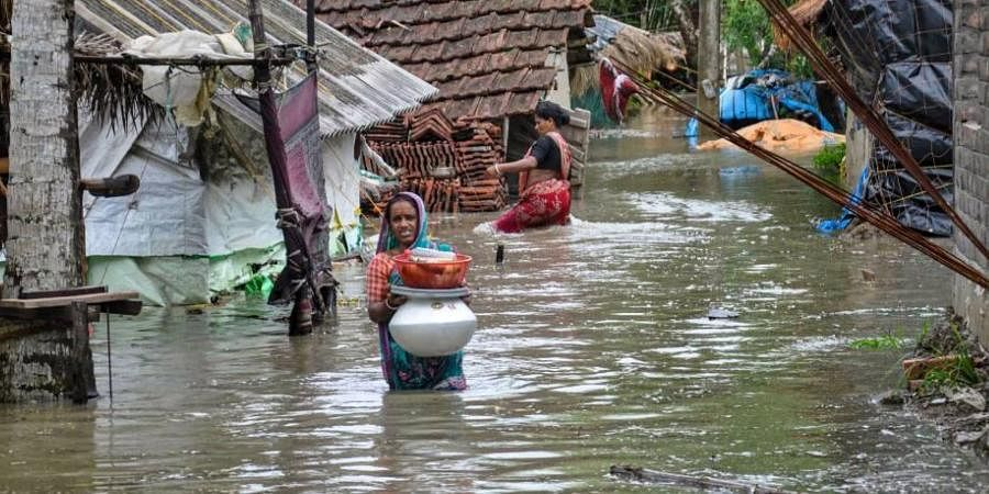 A woman wades through a water-logged road in a village after landfall of cyclone Yaas, in South 24 Paragnas.