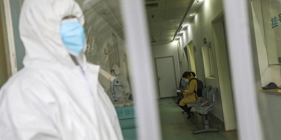 Medical workers in protective gear stand as a woman suspected of being ill with coronavirus waits to be seen at a community health station in Wuhan in central China's Hubei Province, Monday, Jan. 27, 2020.