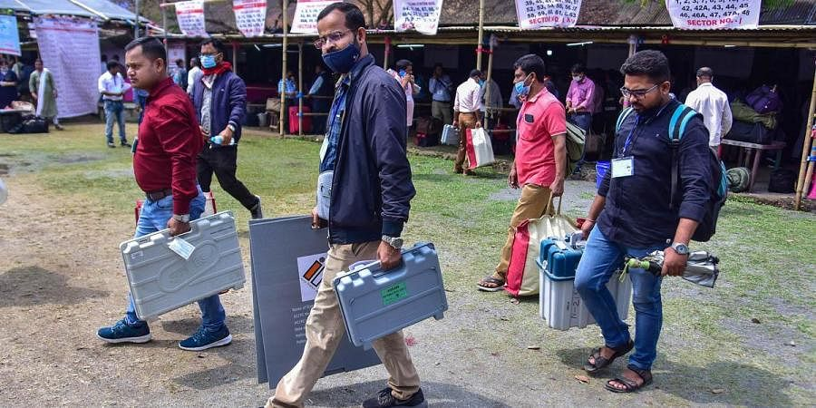 Officials check Electronic Voting Machines (EVM) and other election materials at a distribution centre, on the eve of second phase of Assam assembly election, in Nagaon.