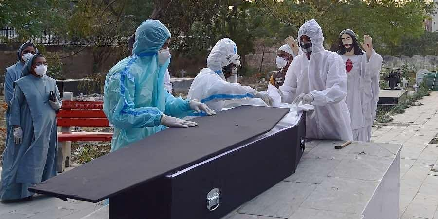 amily members perform the last rites of a person, who died from the coronavirus disease (COVID-19), at a Christian cemetery