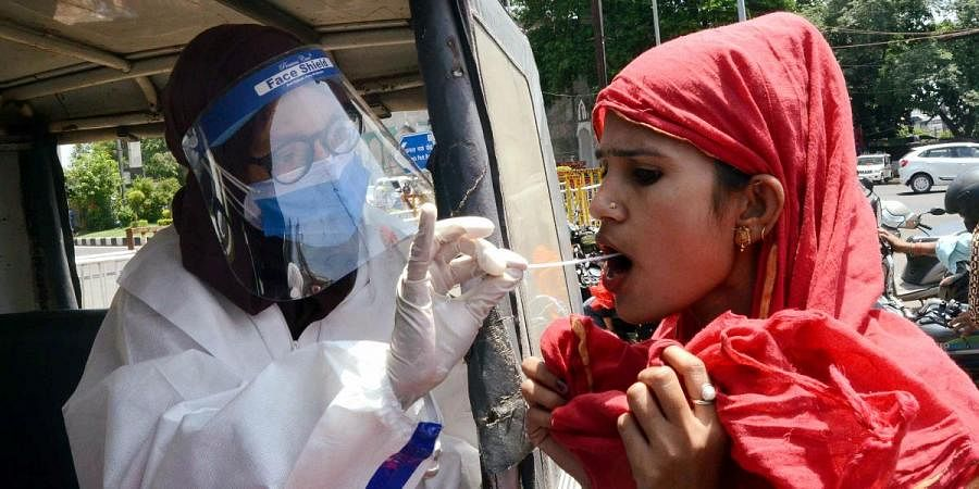 A medic wearing a PPE kit collects a swab sample of a woman for the COVID-19 test in Bhopal