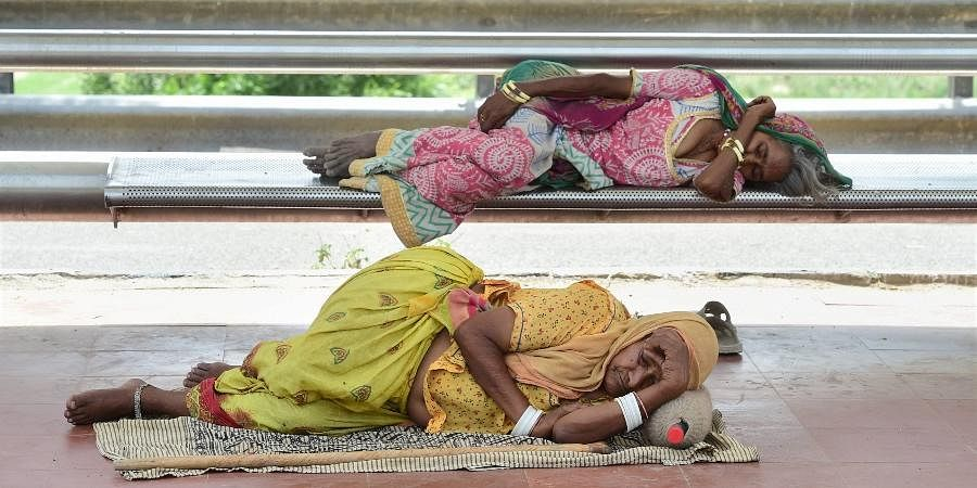 Labourers rest at a bus shed during COVID-induced lockdown, in New Delhi