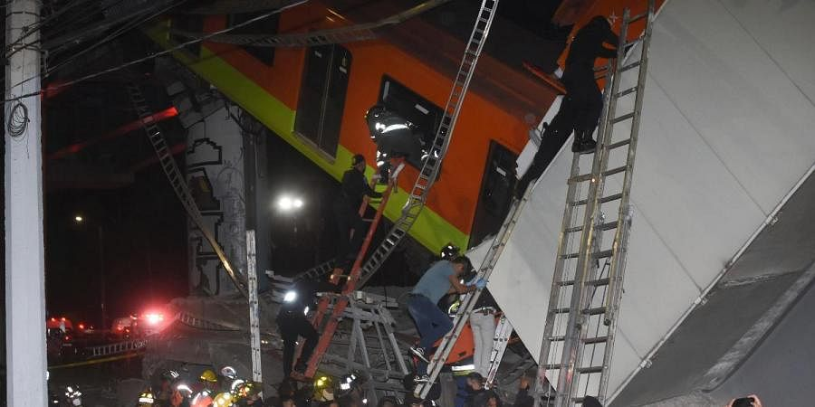 Fire fighters and rescue personnel work to recover victims from a subway car that fell after a section of Line 12 of the subway collapsed in Mexico City