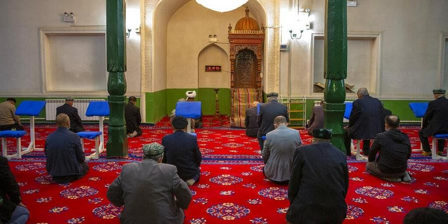 Uyghurs and other members of the faithful pray during services at Id Kah Mosque in Kashgar in western China's Xinjiang, as seen during a govt organized visit for foreign journalists on April 19, 2021.