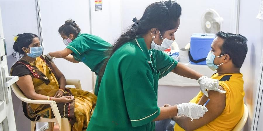 Health workers administer COVID-19 vaccine doses to beneficiaries, at the Jumbo COVID Vaccination Centre, in Mumbai