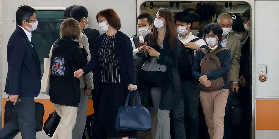 Commuters step out of a train at a station in Tokyo.