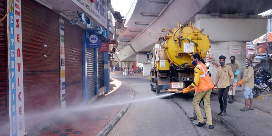 Corporation officials fumigating shops near the Over Bridge in Thiruvananthapuram. (Photo | Vincent Pulickal, EPS)