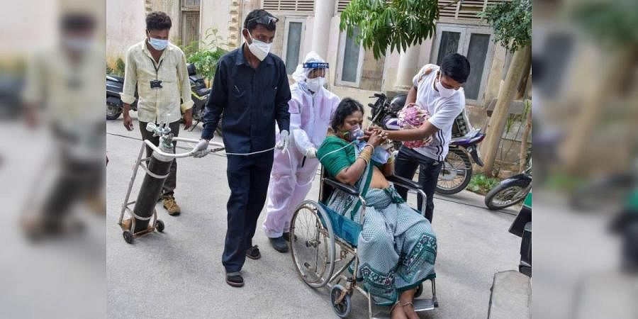 A COVID-19 patient returns back due to non-availability of beds at a hospital, in Hyderabad