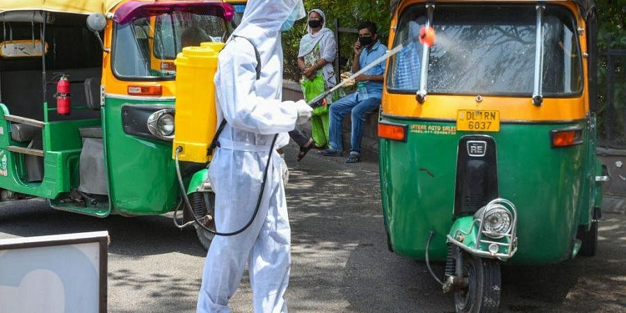 A health worker wearing a PPE kit sanitizes auto-rickshaws, during the ongoing Covid-19 lockdown, in New Delhi (Photo   PTI)