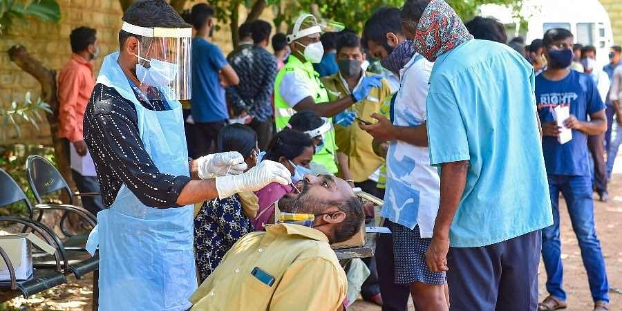 A medic collects a swab sample from a man for the Covid-19 testing, in Bengaluru