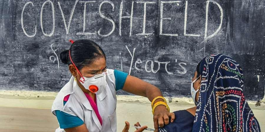 A medic inoculates a dose of a Covid-19 vaccine to a woman, at a vaccination centre, in Ajmer