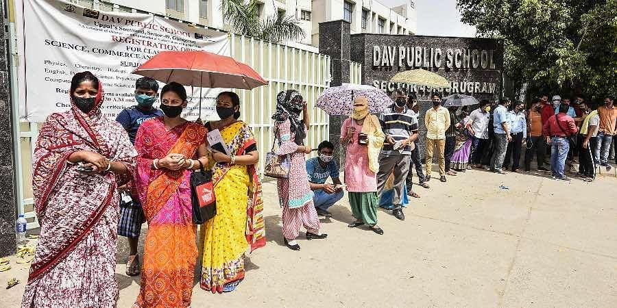 Beneficiaries wait in a queue to receive the COVID-19 vaccine dose, at a vaccination camp at DAV School Sector 49, in Gurugram