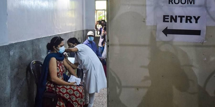 A health worker administers a dose of the COVID-19 vaccine to a woman, at a vaccination centre in Kolkata.