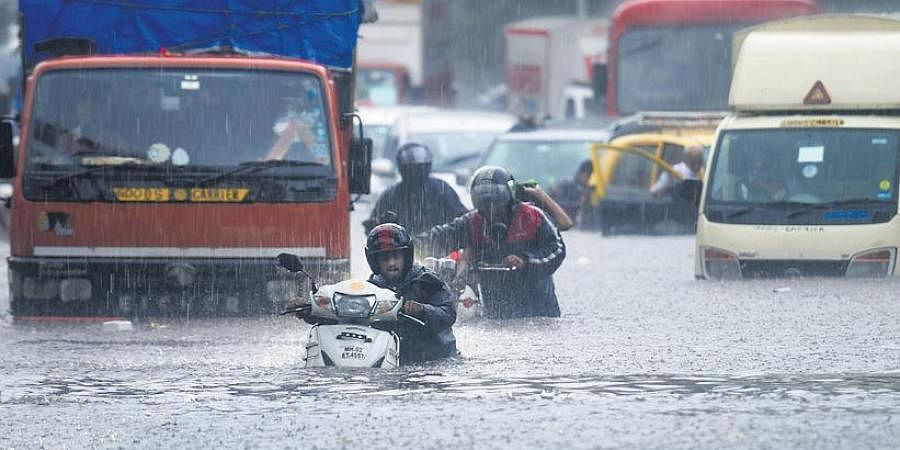 Vehicles make their way through a waterlogged road during heavy rain, at Kings Circle, in Mumbai.