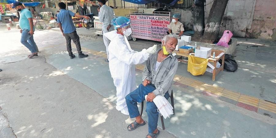 A healthcare worker collects swab sample of a man for Covid testing in Delhi on Wednesday.