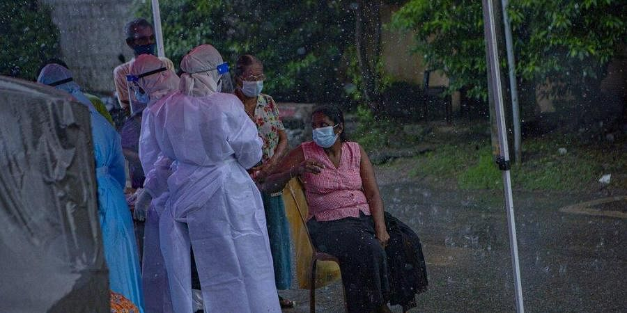 Sri Lankan health officials collect swab samples from people to test for the coronavirus during a brief spell of rain in Colombo