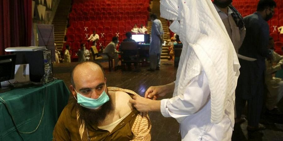 A government employee receives the Convidecia COVID-19 vaccine from a paramedic at a vaccination center in Nishtar hall, in Peshawar, Pakistan