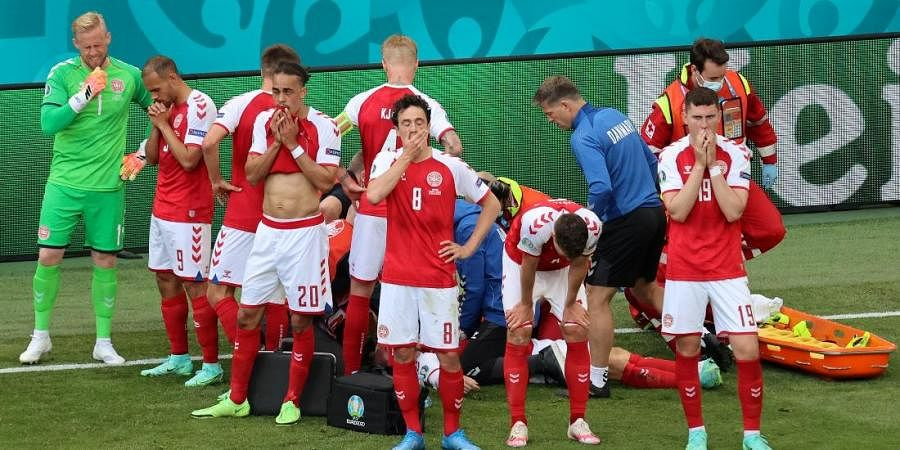 Denmark's players react as their teammate Christian Eriksen lays injured on the ground during an Euro 2020 match in Copenhagen