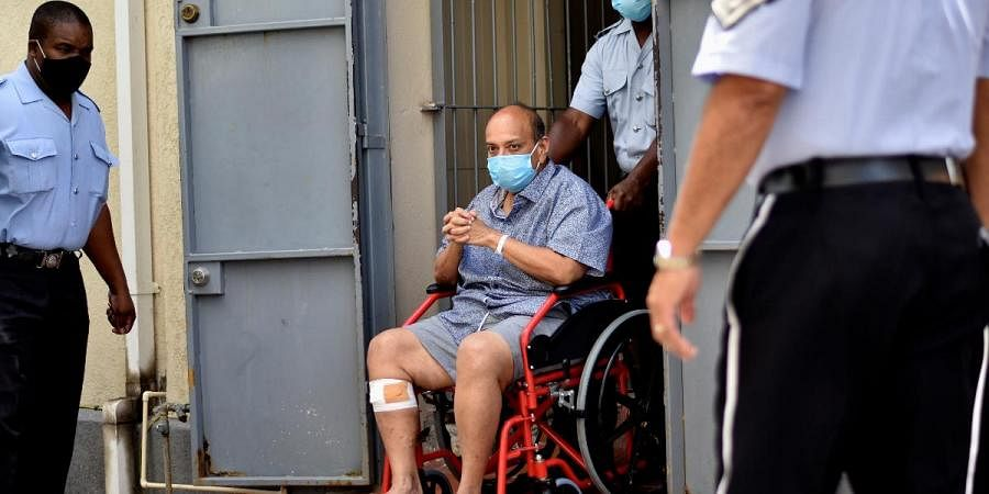 Antigua and Barbuda businessman Mehul Choksi exits in a wheelchair the magistrate's court in Roseau