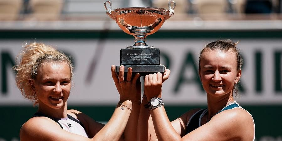 Barbora Krejcikova (R)and compatriot Katerina Siniakova hold the cup after defeating Bethanie Mattek-Sands and Iga Swiatek in their women's doubles final match of the French Open.