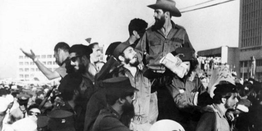 The Cuban rebel leader Fidel Castro (C), next to the members of his leftist guerrilla movement '26th of July Movement' Camilo Cienfuegos (on top with hat) and Ernesto 'Che' Guevara (R with beret), waves from a jeep 08 January 1959, entering La Havana after the victory over the forces of Cuban dictator Fulgencio Batista.
